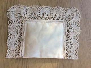 Close up of vintage hand stitched sewn lavender pillow antique lace & border beautiful patterned hand tatted ornate cotton stitching filled organic scented relaxing healing flowers wood background