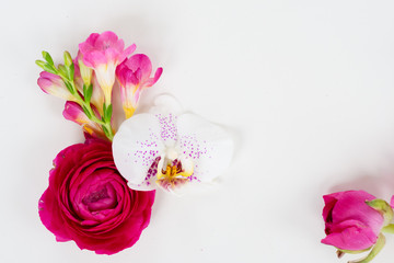 Flowers composition made of fresh orchid and ranunculus on white background. Flat lay, top view, copy space