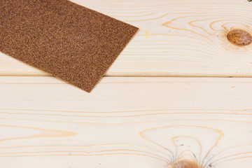 Wall Mural - close-up of sandpaper on wooden plank