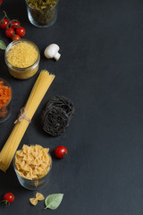 Different types of Italian pasta with vegetables on the dark chalkboard