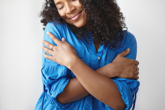 Cropped shot of charming gorgeous young Afro American female with black curls and plush lips keeping eyes closed and smiling with pleasure, embracing herself while dancing to romantic music
