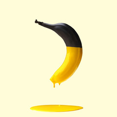Black banana with dripping yellow paint on light yellow background. Creative food concept.