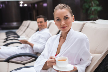 Focus on waist up portrait of delighted woman sitting on deckchair and resting after hydrotherapy. She is wearing bathrobe and holding cup of hot drink. Smiling man is looking at her on background