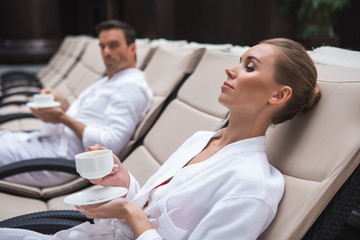 Side view focus on relaxed female lying on deckchair in bathrobe with cup of coffee in hands. Attractive man looking at her and sitting nearby is on background