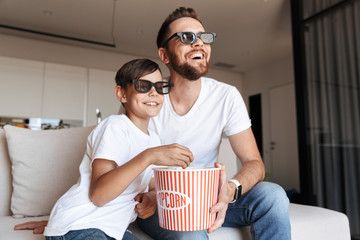 Image of caucasian man 30s and boy 8-10 wearing 3d glasses eating popcorn and smiling, while sitting on couch at home and watching movie