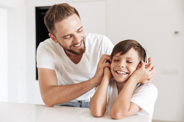 Portrait of caucasian father 30s and son 8-10 smiling together, while resting at home and listening to music via wireless headphones