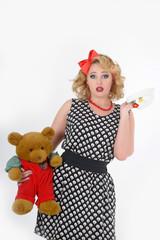 woman blonde in polka-dot dress with teddy bear in hands