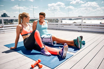 Sporty couple is sitting and resting after joint training. They are exercising with dumbbells on open balcony in city center. Smiling woman is talking to man while is listening to her attentively
