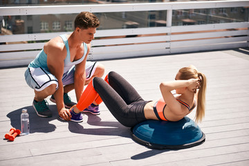 Fit lady is doing abdominal crunches while lying on half-ball on open balcony. Man is assisting her by holding her feet. Training together for better results concept