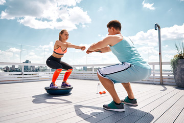 Strong man is doing sit-ups while girlfriend is squatting on fitness half ball and using resistance band on thighs. They are having joint work out on sunny terrace in city center under blue sky