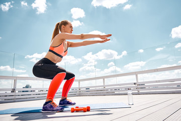 Sporty woman is doing squats on roof top of urban house. She is straightening arms forward and looking far away. Female is using also dumbbells and bottle of water for training in warm weather