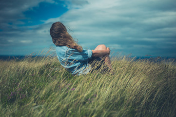 Young woman sitting in field on windy day