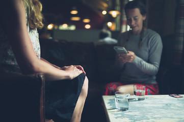 Two women drinking water in cafe