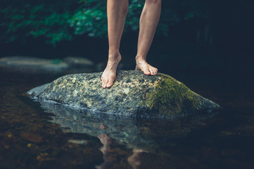 The feet of a young woman on a rock in the river