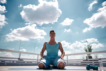 Low angle of strong athlete is kneeling on sunny terrace and putting hands on legs. He is closing eyes for relaxing after exercising with dumbbells. Refreshing mind and body after work out concept
