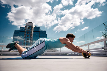 Strong man is doing knee roll outs with abs wheel. He is exercising on sunny terrace of high building among downtown. Work out with sport outfit in open air concept