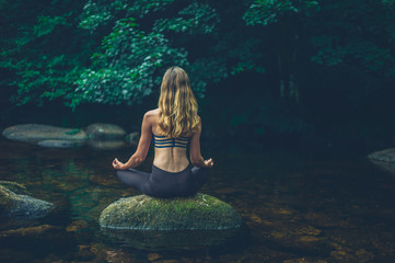 Woman meditating on rock in river