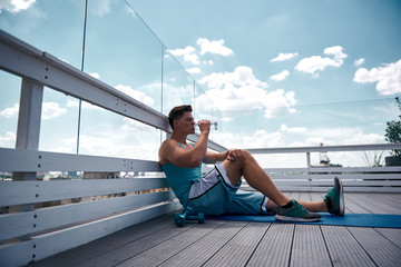 Shredded man is sitting on mat and resting after training. He is exercising with dumbbells on terrace of high house. He is sipping still drink from bottle for refreshment and leaning against railing