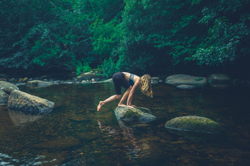 Young woman climbing a rock in the river