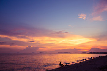 Sunset beach and twilight sky with silhouette relaxing tourist people
