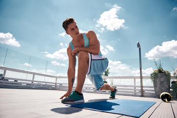 Low angle of strong sportsman training flexibility and strength on rooftop in city center. He is doing lunges on mat and looking aside with concentration. Male is keeping sport outfit besides for