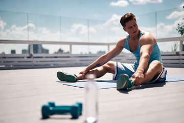 Tired sportsman is sitting on mat and relaxing. He is training with dumbbells on roof top of city building. Male is having bottle of water nearby for quenching thirst