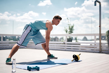 Ripped guy is doing lunges for improving flexibility and warming muscles. He is training with dumbbells and ABS roller. Work out indoors in urban atmosphere concept
