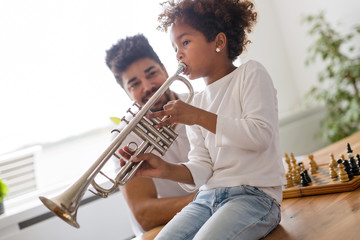 Girl with her father learning trumpet Wall mural
