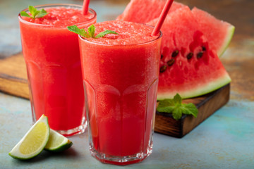 Watermelon slushie with lime, summer refreshing drink in tall glasses on a blue rusty background