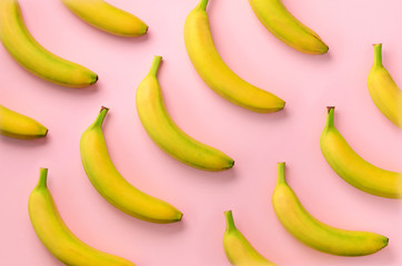 Colorful fruit pattern. Bananas over pink background. Top view. Pop art design, creative summer concept. Minimal flat lay style.