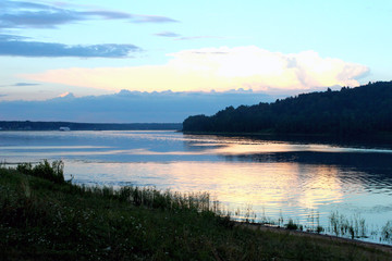 Volga river and forest on blue sky background. Sunset. Horizontal view.