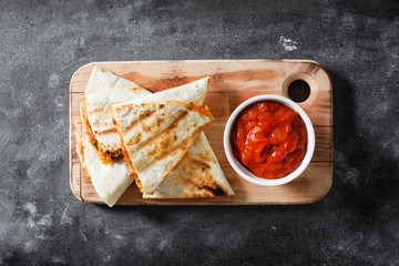 Mexican quesadilla with chicken, cheese and peppers on black slate. Top view