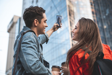Profile of smiling female and male looking at each other. Young excited man is making picture of building with phone. They are holding plastic cups in hands and laughing in delight