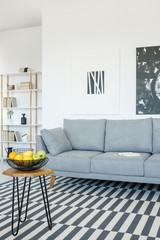 Grey sofa and table on patterned carpet in bright living room interior with posters. Real photo