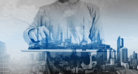 a man working on digital tablet, with power plant, oil refinery industry factory buildings hologram