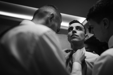 handsome groom posing while stylish groomsman helping him to get ready in the morning. wedding preparation. friends having fun