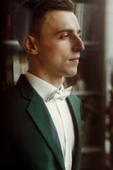 Smiling, handsome brunette groom in stylish suit and white bowtie posing for portrait, morning wedding preparation in hotel room, face closeup