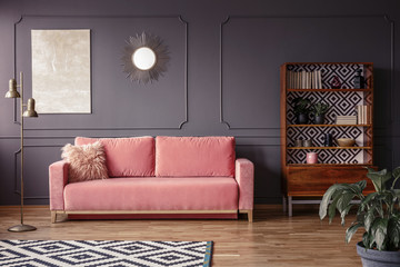 A marble beige painting and a sunburst golden mirror on a gray wall with molding in a stylish living room interior with a velvet, powder pink sofa and retro furniture