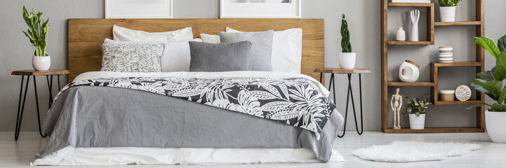 Real photo of wooden double bed with floral sheets standing in grey bedroom interior with fluffy rug and rack with decor