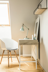 Lamp on desk in white workspace interior on attic with chair and