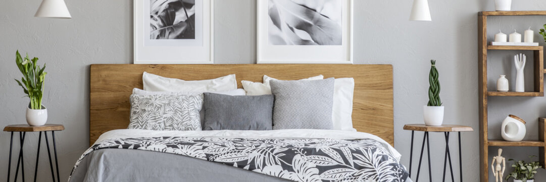Floral bedclothes on double bed with wooden headboard standing in real photo of bedroom interior with two posters and fresh plants