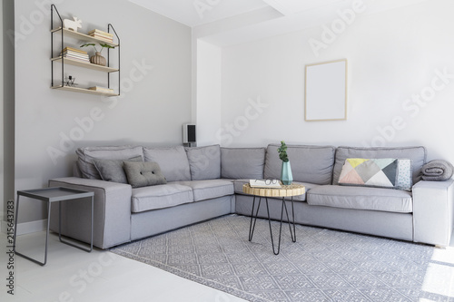 Grey corner sofa and wooden table in spacious living room ...