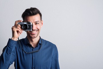Portrait of a young man in a studio with a camera on front of his eye. Copy space.