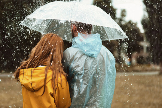 Male and female strolling under one umbrella together. They are bonding to each other with backs turned enjoying wet weather