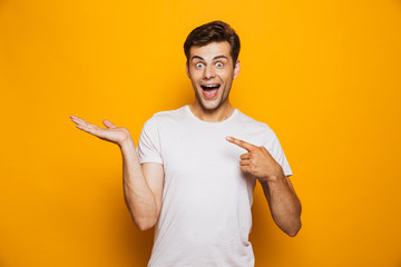 Portrait of a cheerful young man pointing fingers away