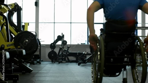 Tilt up of disabled man in wheelchair doing workout with battling