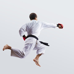 An athlete in white karategi and red overlays on his hands beats blow hand in the jump