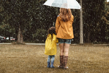 Full length of woman holding hands with small child. They are standing under umbrella with turned backs outside. Copy space in left side