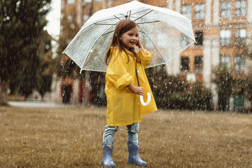 Full length of happy small girl holding umbrella outside. She is enjoying weather outdoors with content