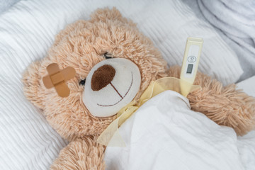 Sick Teddy bear with plaster and thermometer is lying in bed.